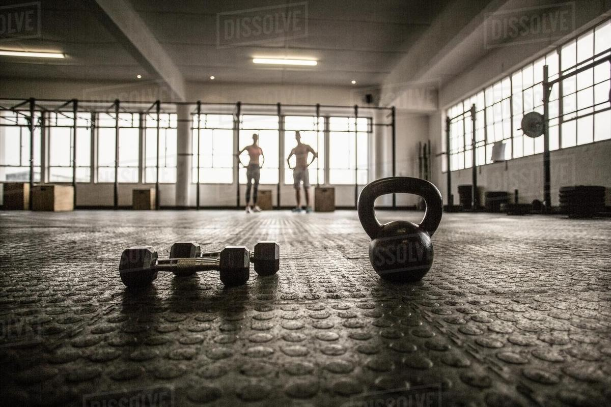 Two fit people on the background in gym   Stock Photo   Dissolve 1200x800