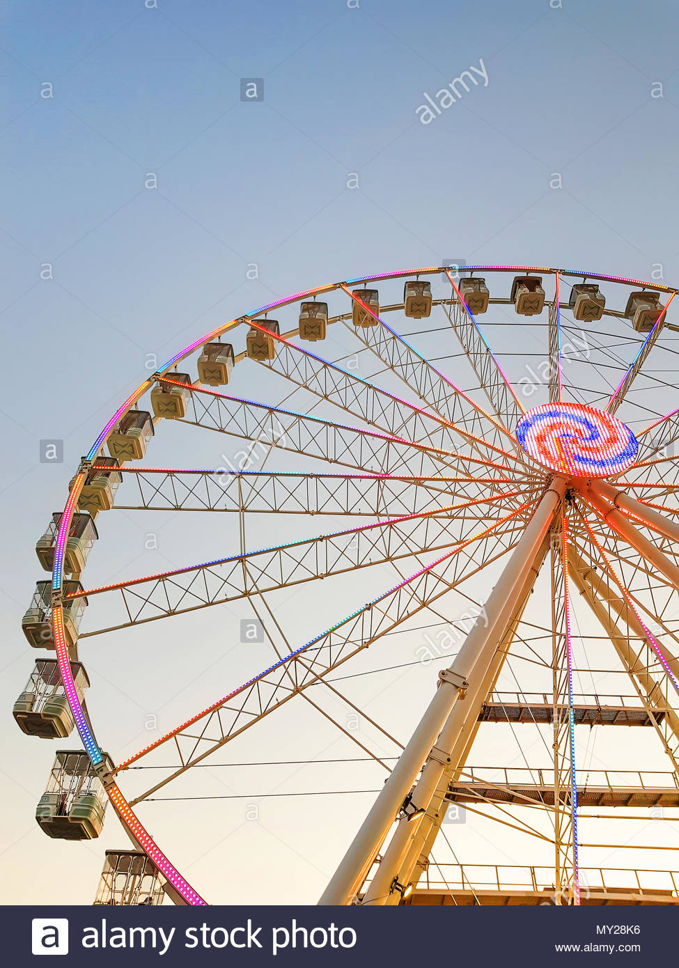 Part of ferris wheel against a blue sky background with colorful 975x1390