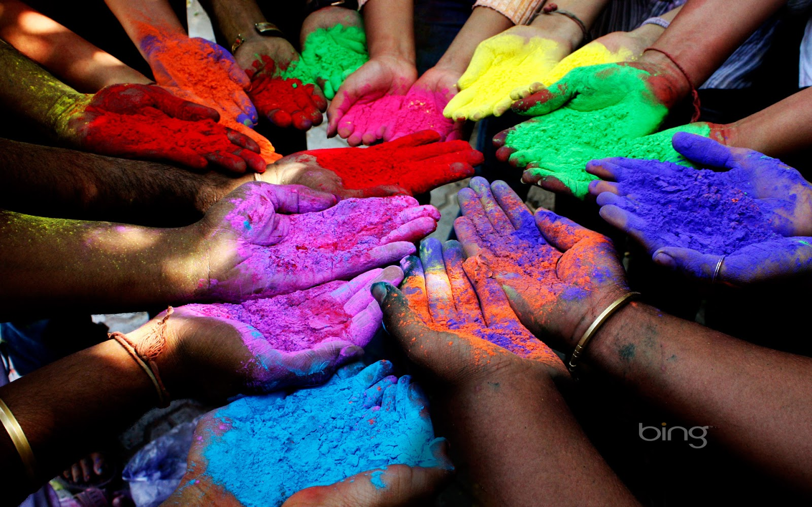 People holding colored powders to celebrate Holi Festival of Colors 1600x1000