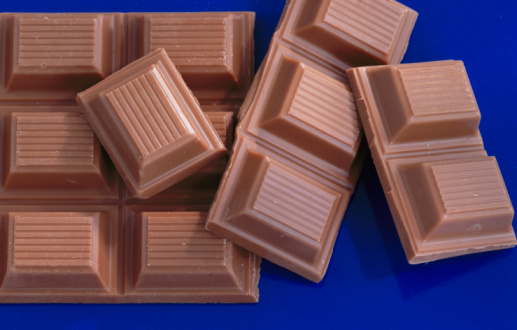 Broken Bar Of Chocolate On Blue Background Closeup Elevated View Stock 517x330