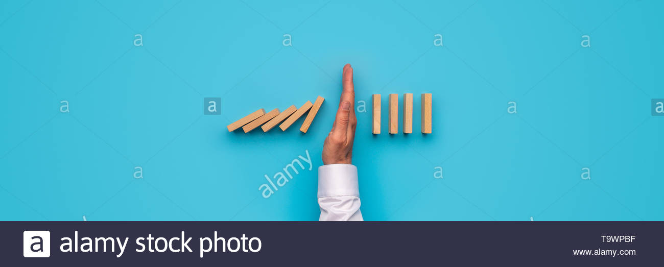 Wide view image of male hand stopping falling dominos Over blue 1300x523