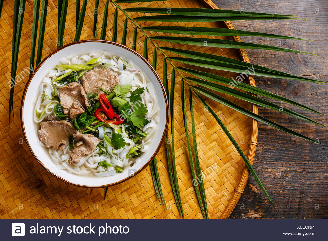 Pho Bo vietnamese Soup with beef on bamboo tray on wooden 1300x956