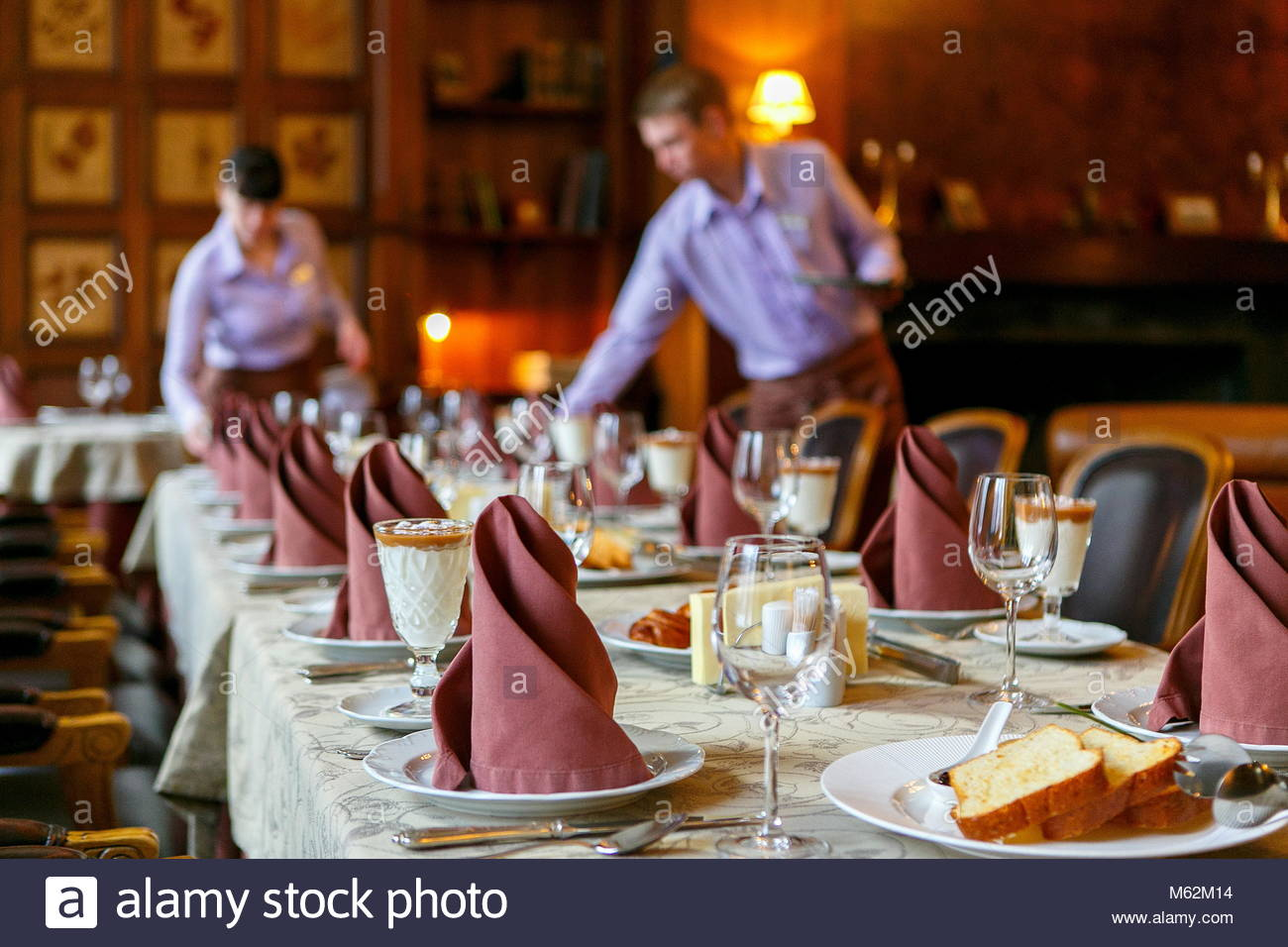 Waiters prepare a table for breakfast Background The foreground 1300x956