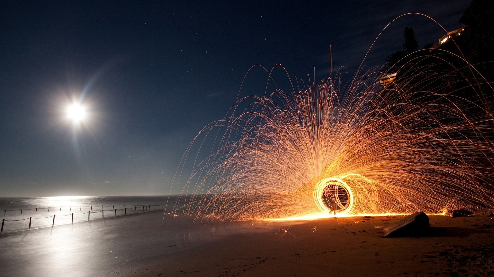 Circular sparkler on a beach at night wallpaper 1920x1080
