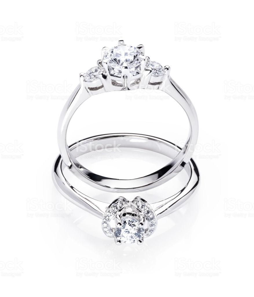 Two Diamond Engagement Wedding Rings On Isolated White Background 877x1024