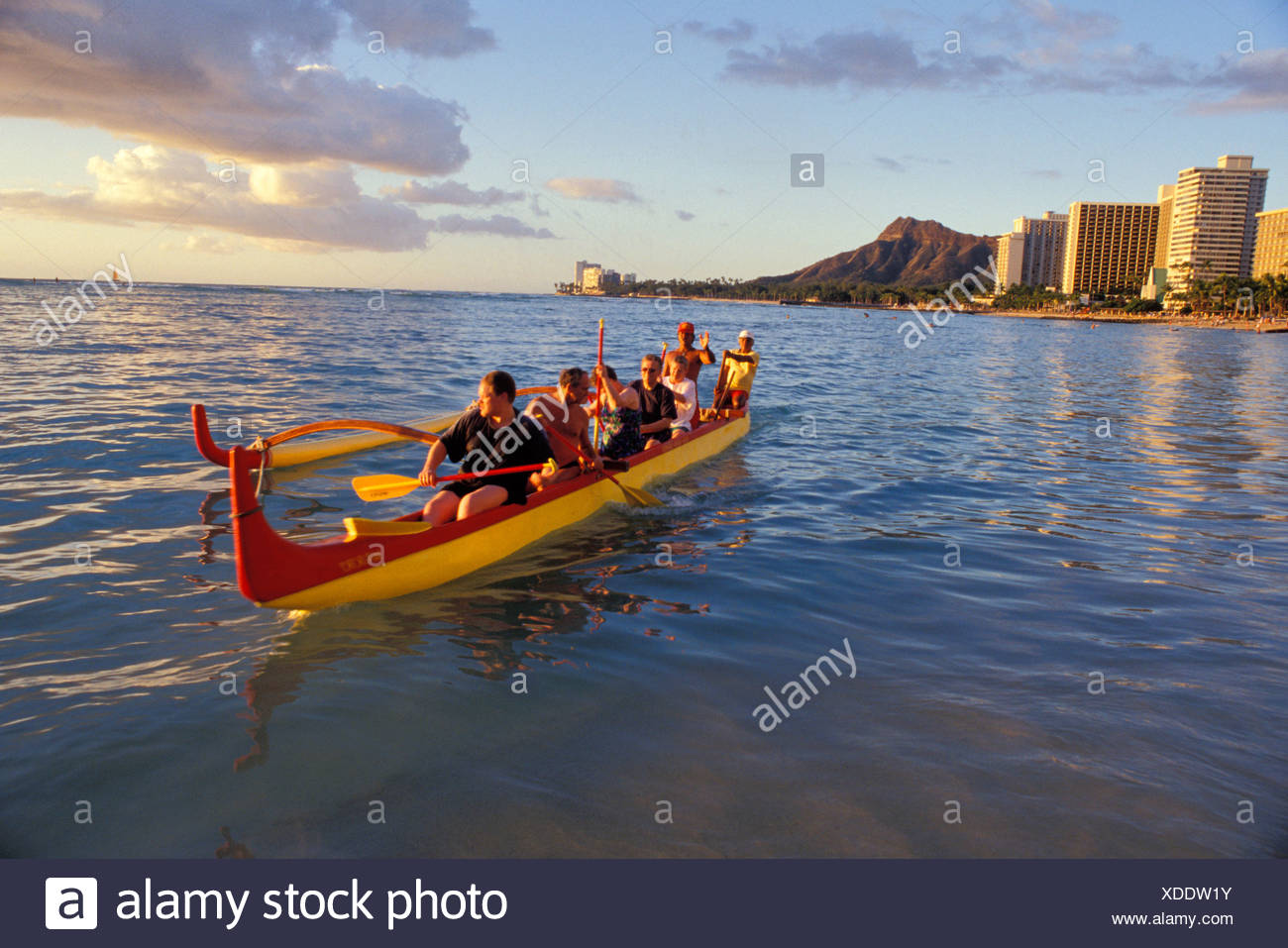 Tourists paddling an outrigger canoe off Waikiki with Diamond Head 1300x957