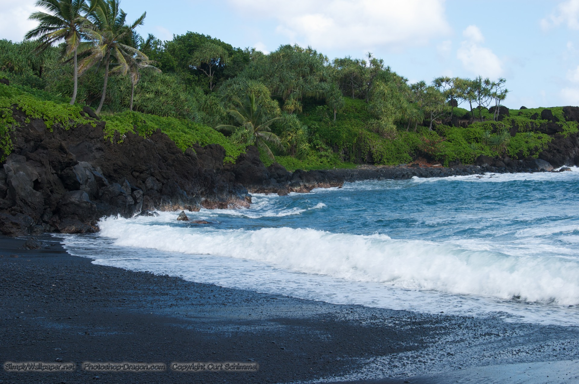 Waves break on shore of this black sand beach with lush tropical 1920x1275
