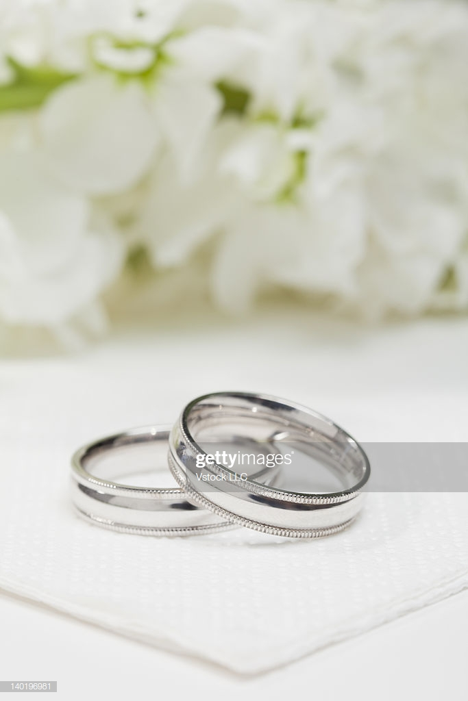Closeup Of Wedding Rings With White Flowers In Background High Res 683x1024