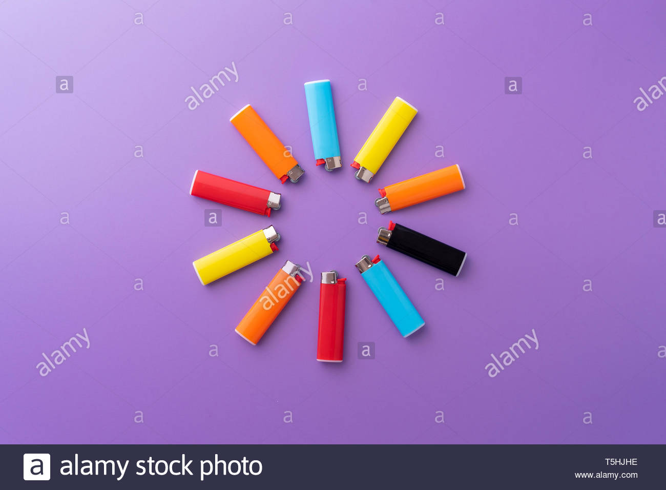 Multiple colorful lighters organized in a circle over purple 1300x956