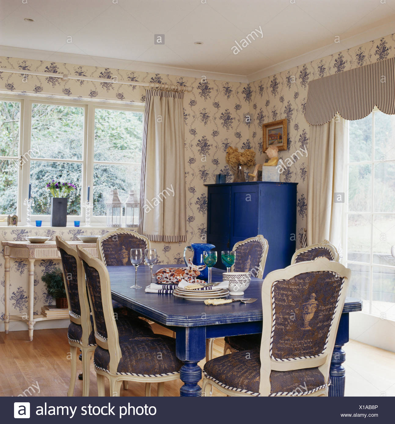 Upholstered white chairs and painted blue table in country dining 1293x1390