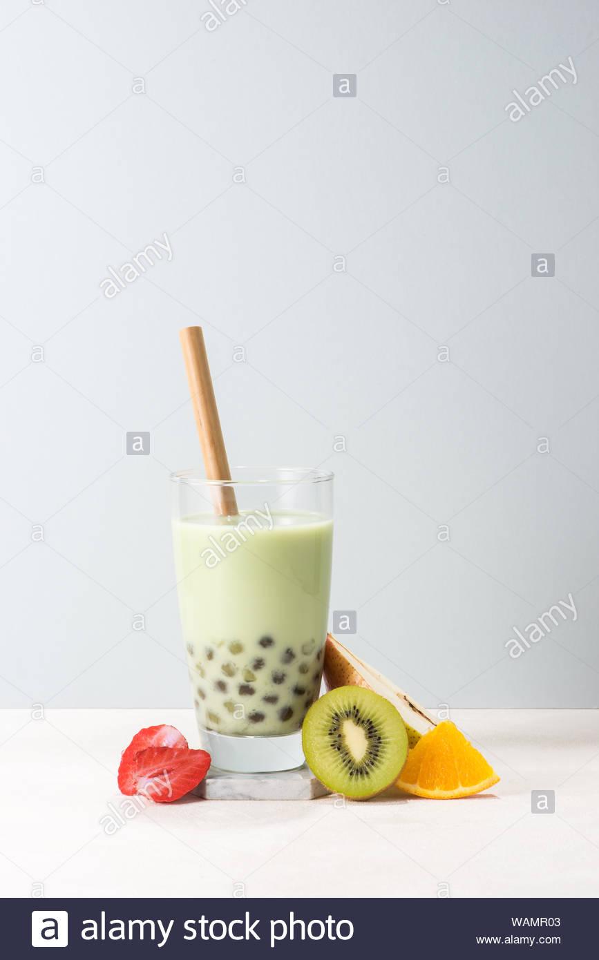 Boba buble tea glass with kiwi strawberry orange slices on blue 867x1390