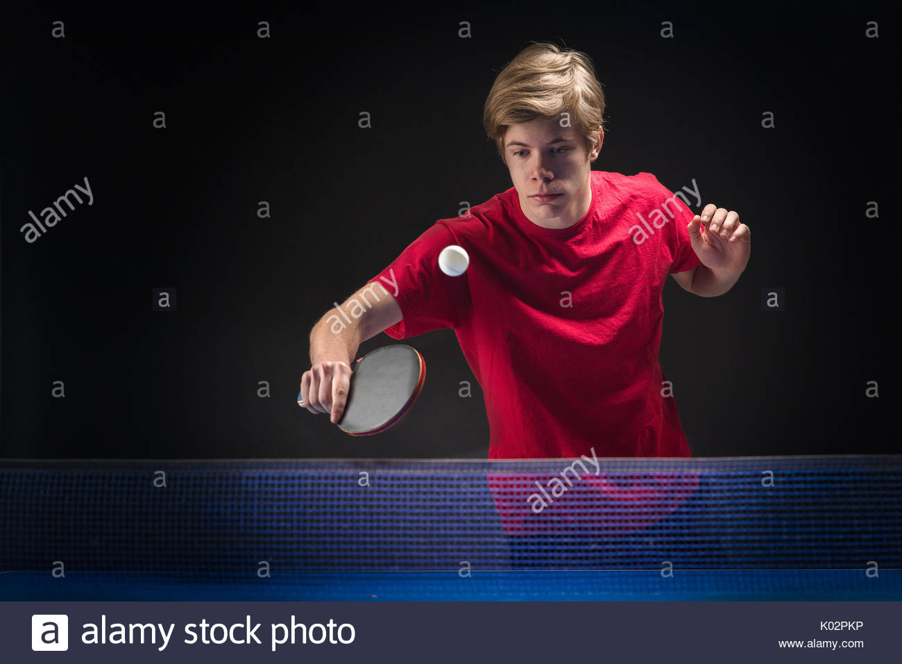 young man tennis player in play on black background Stock Photo 1300x956