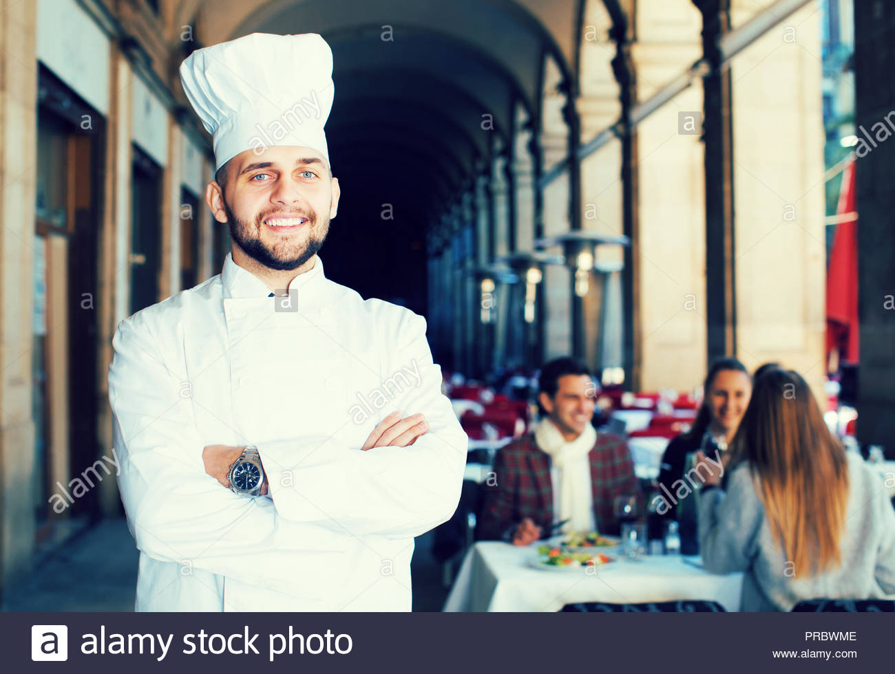 Portrait of glad professional chef on background with restaurant 1300x980