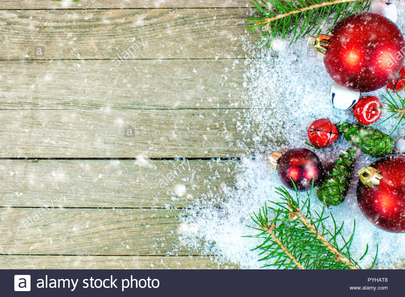 closeup of Christmas decoration with snow falling on wooden 1300x956