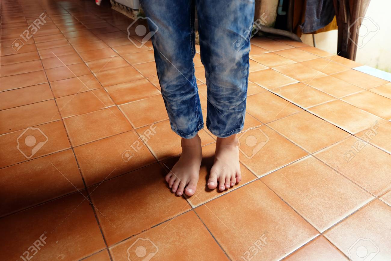 Close Up Boy Barefoot Wear Blue Jeans On Tile Background Great 1300x866