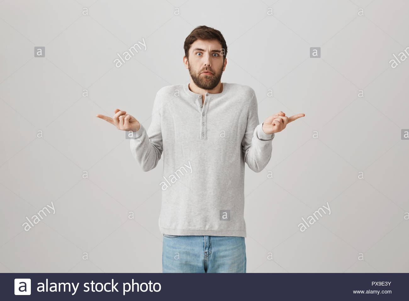Portrait of puzzled good looking man pointing at both sides and 1300x956