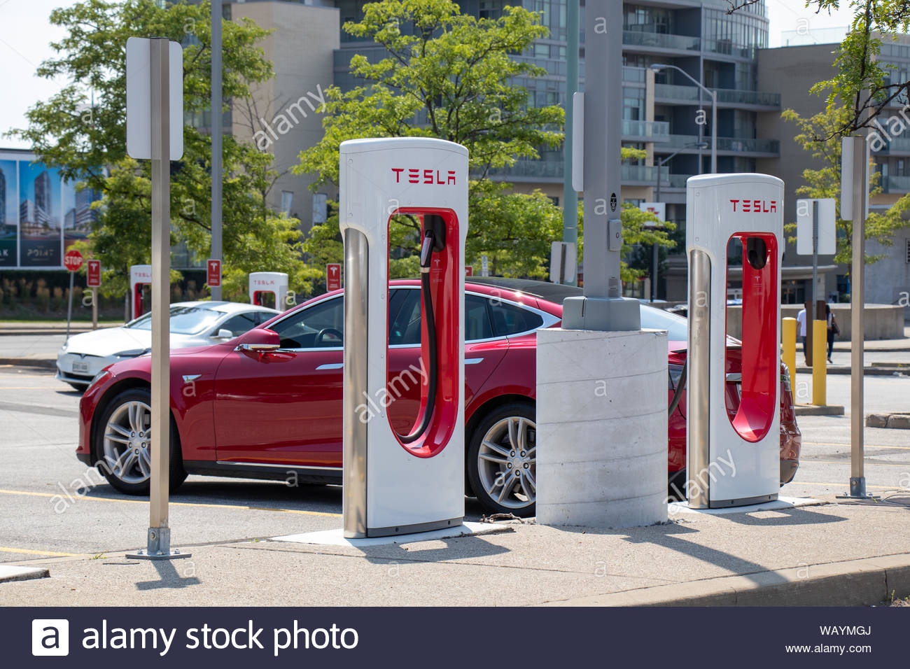Tesla Supercharger Station seen with red Tesla Model S and white 1300x956