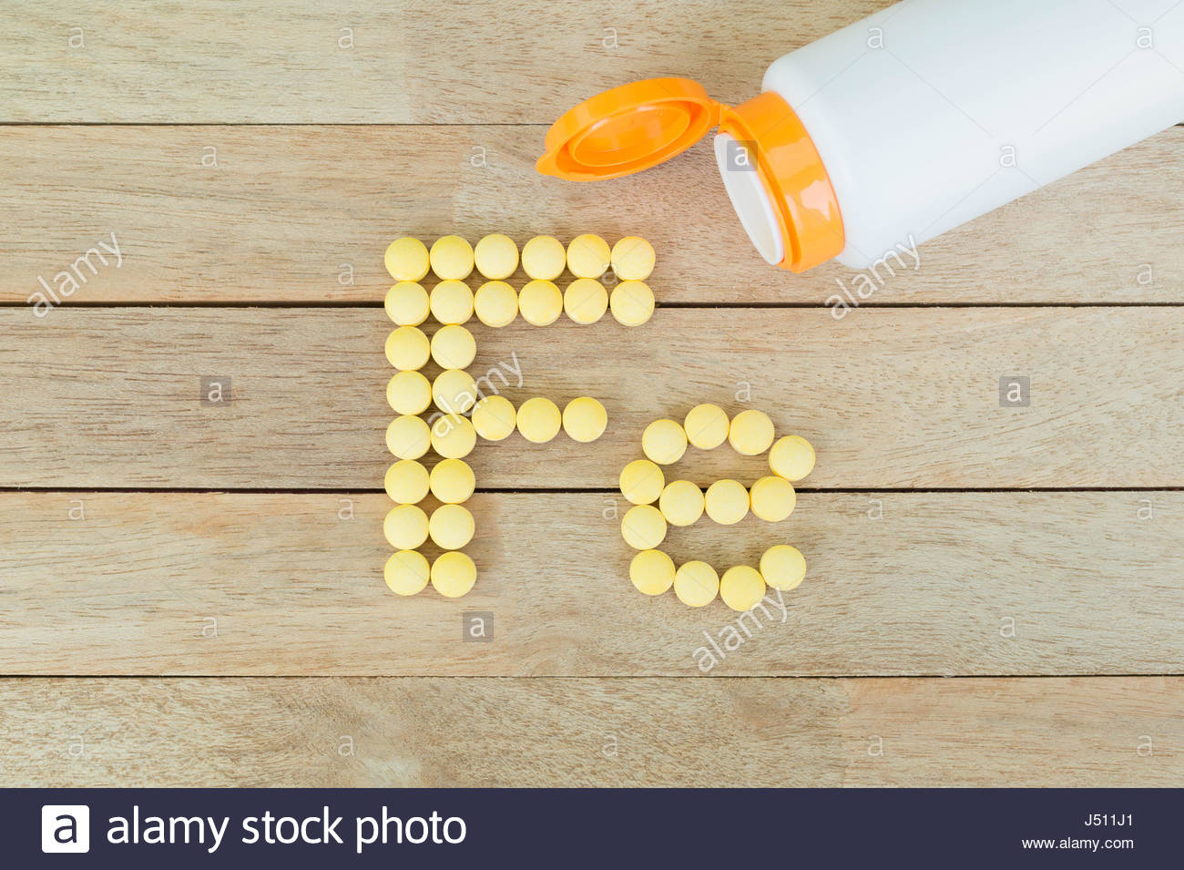 Yellow pills forming shape to Fe alphabet on wood background Stock 1300x955