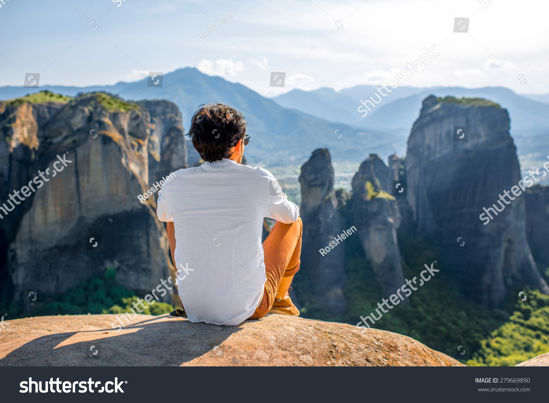 Welldressed Man Sitting On Rocky Mountain Stock Photo Edit Now 1500x1101