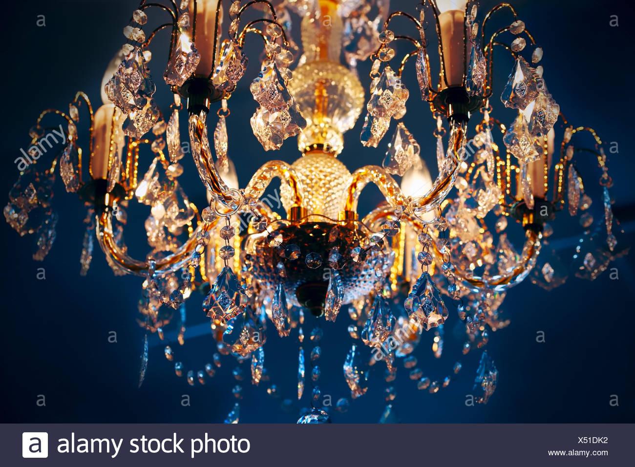 Elegant crystal chandelier hanging against blue background Stock 1300x956