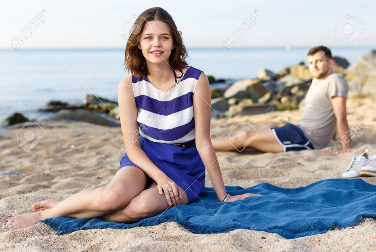 Glad Girl Sitting On The Beach Man On The Background Stock Photo 1300x872