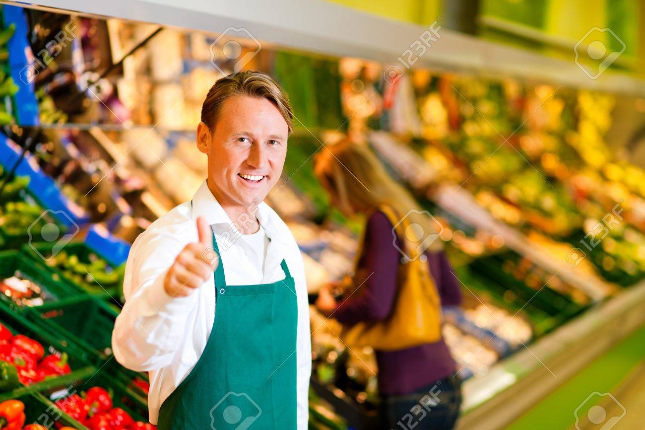 Shop Assistant In A Supermarket At The Vegetable Shelf In The 1300x866