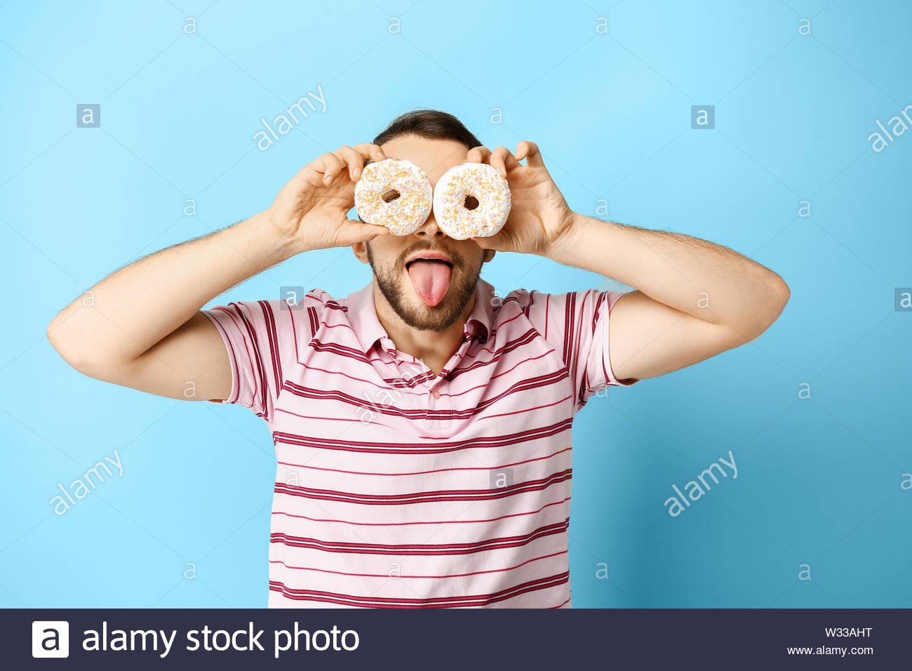Funny man with donuts on color background Stock Photo 260073684 1300x956
