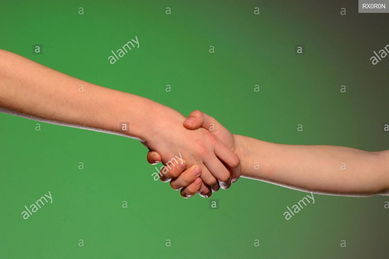 Two hands handshake isolated on a green background symbolizing 1300x867