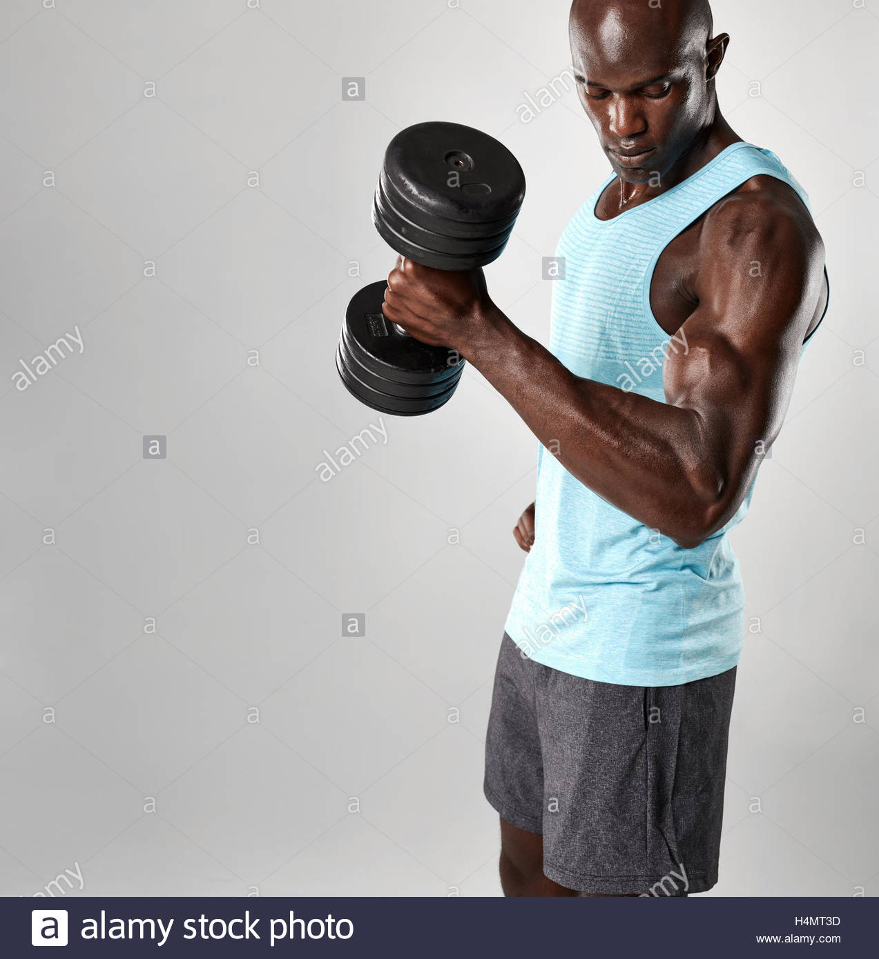 Fit young african man exercising with dumbbells against grey Stock 1273x1390