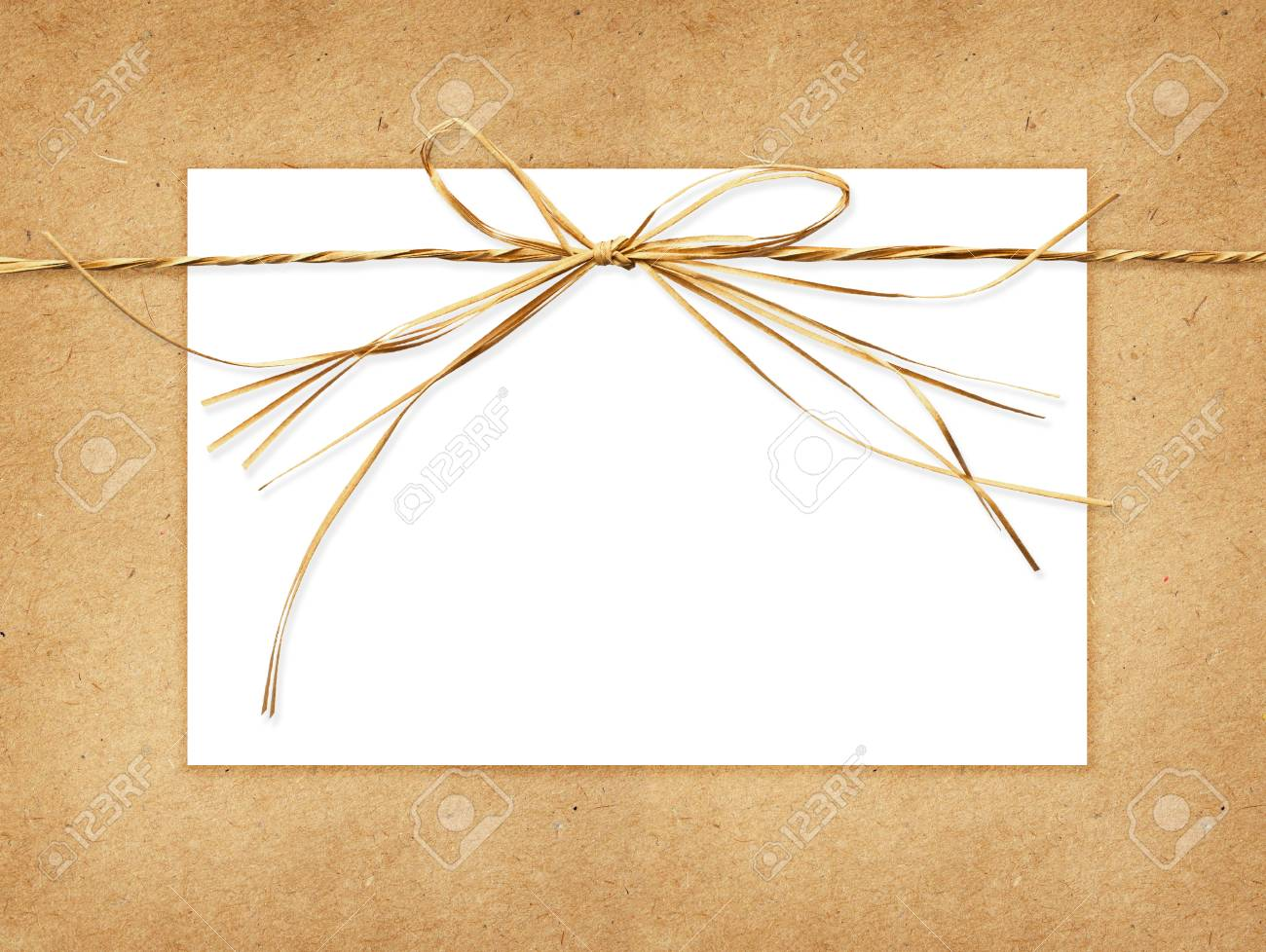Beige Raffia Bow And A Card Tied On Craft Paper Background Stock 1300x978
