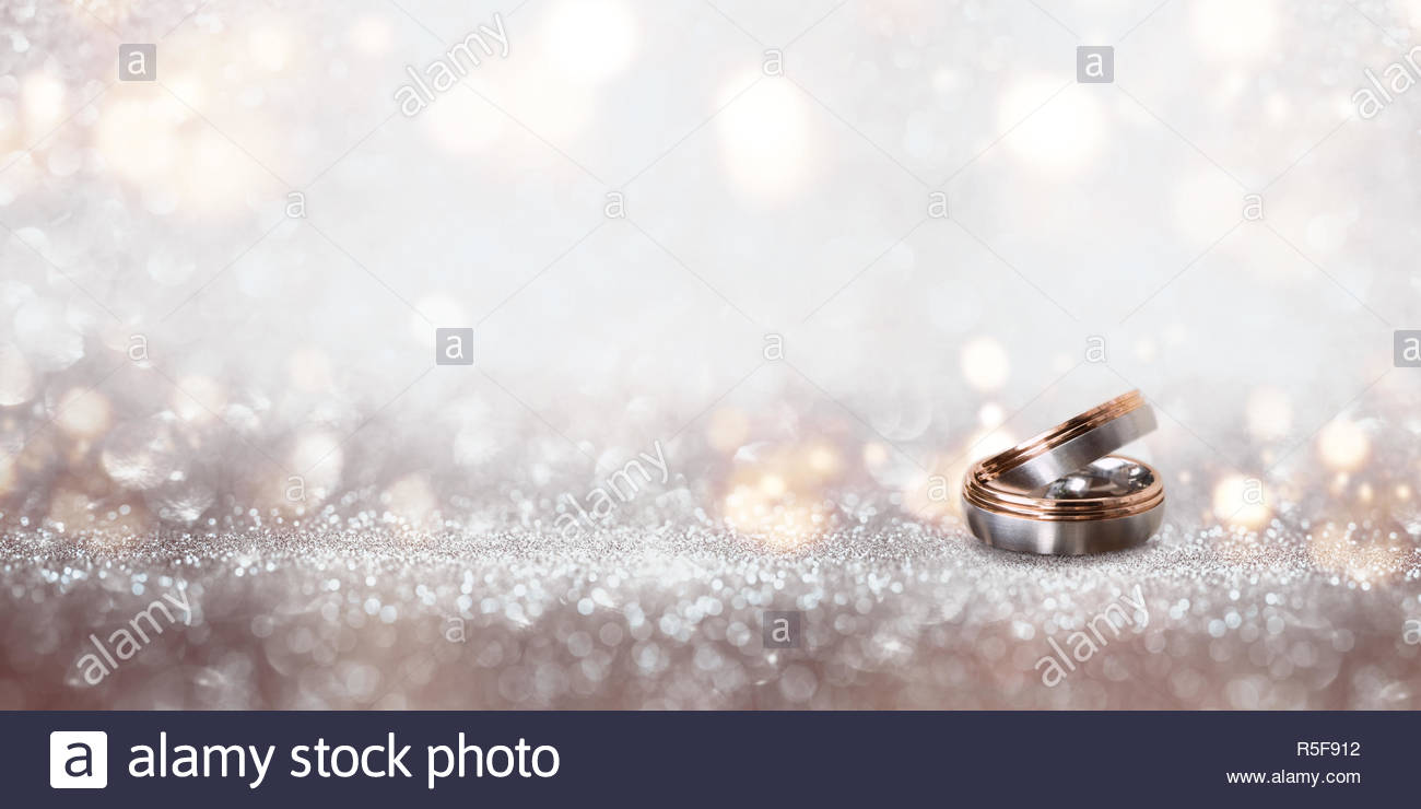 wedding rings on an abstract silver glittering bokeh background 1300x740