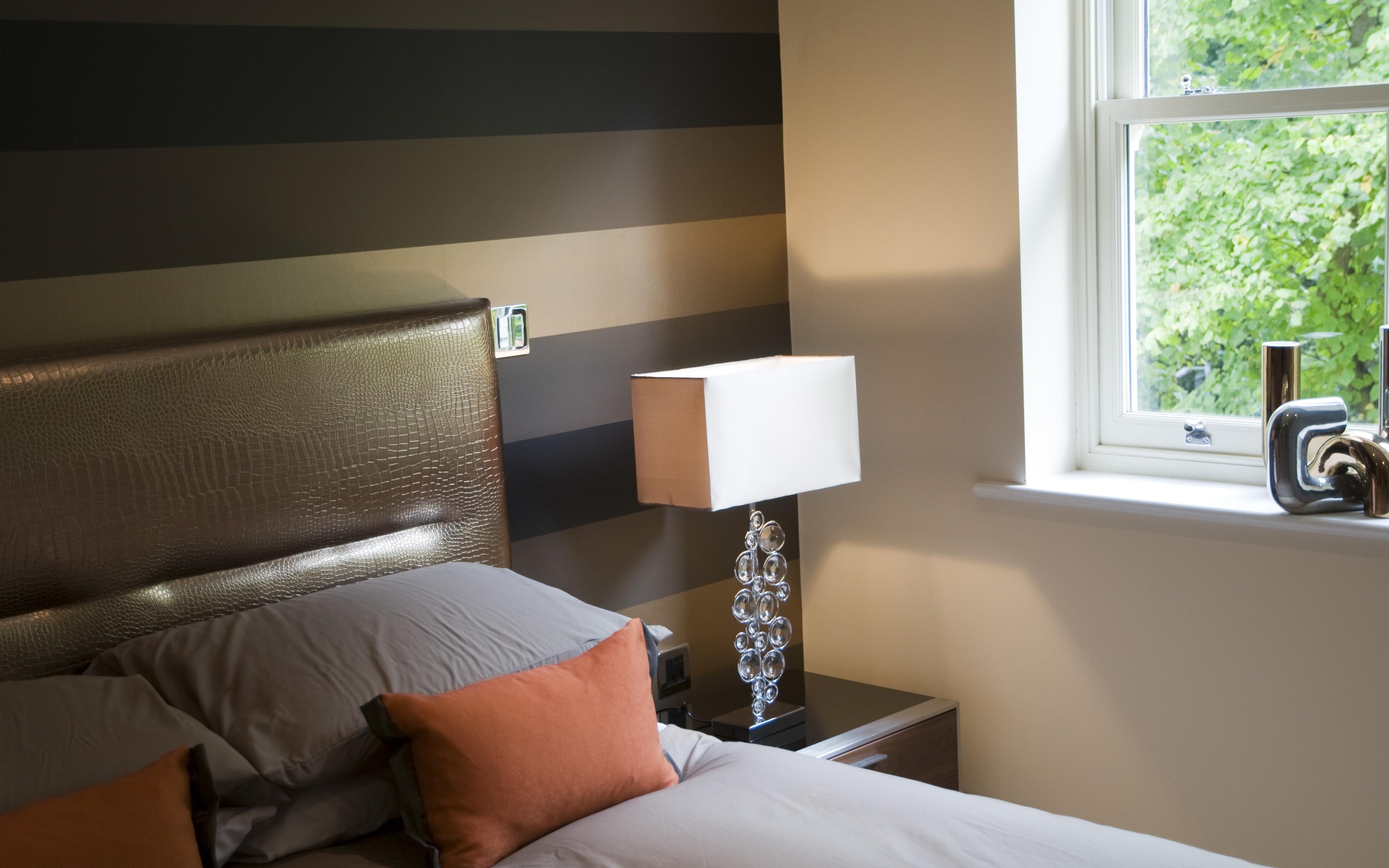 Horizontal striped wallpaper sits behind a bespoke fauz croc skin 3998x2499