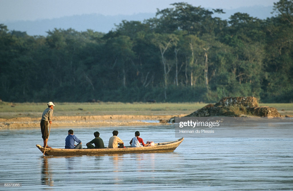 People In Canoe On River With Forest In Background Royal Chitwan 1024x667