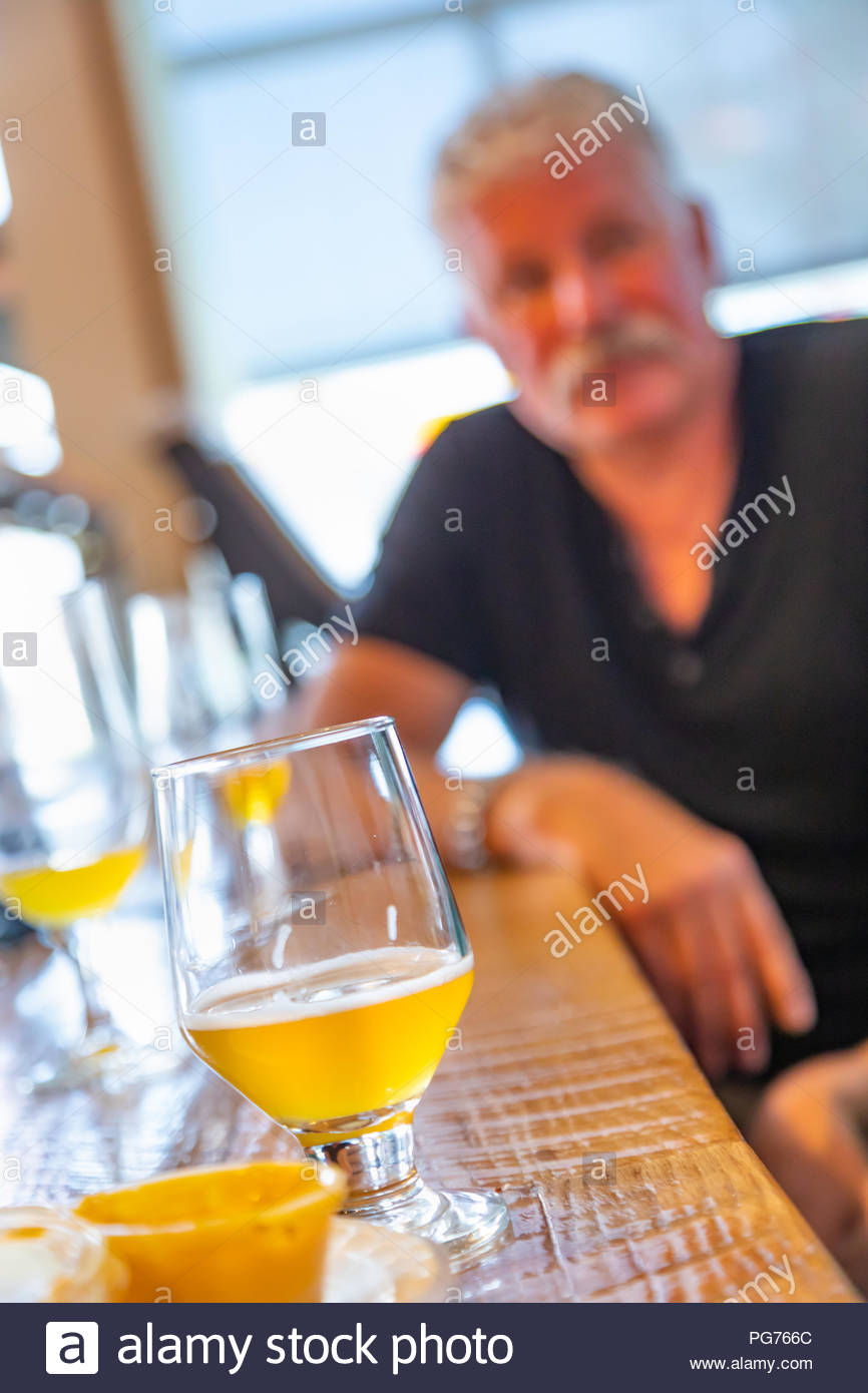 Glass of Micro Brew Beer On Bar With Handsome Man In Background 866x1390