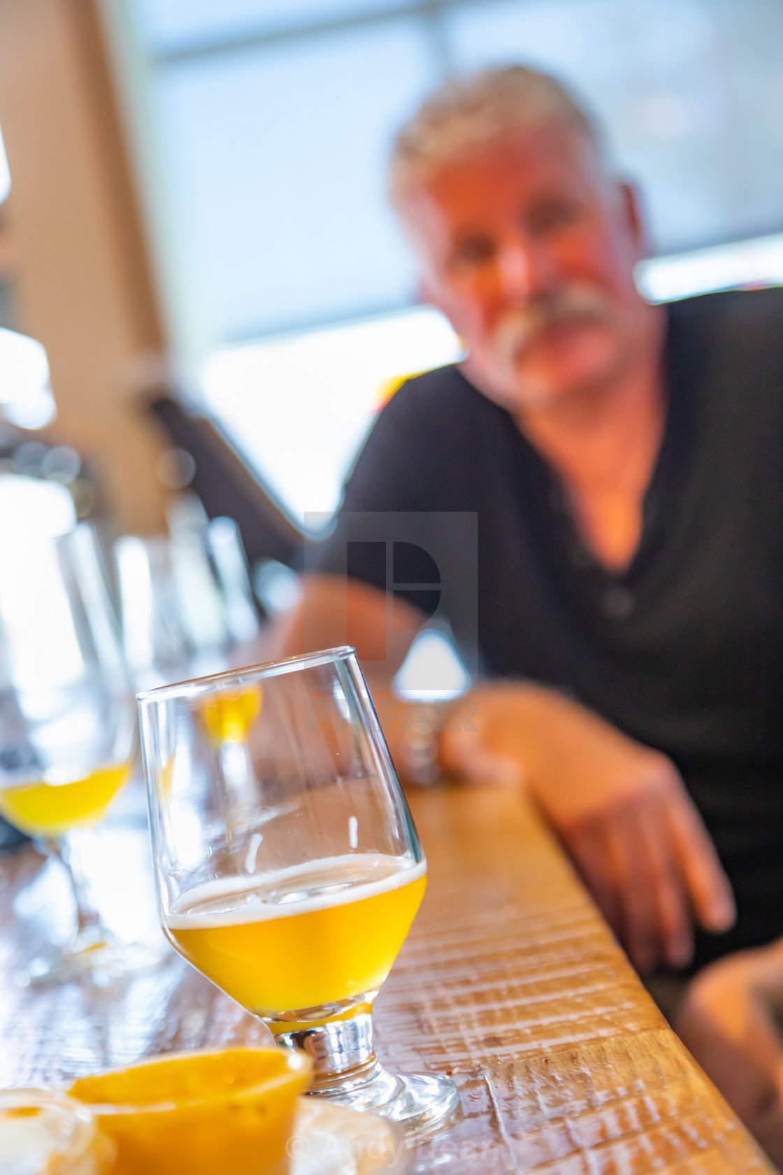 Glass of Micro Brew Beer On Bar With Handsome Man In Background 1120x1680