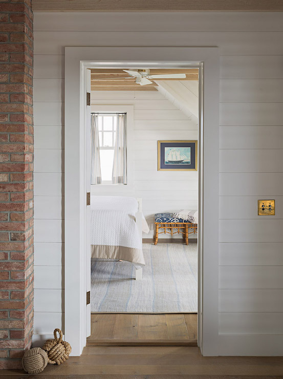 Hallway to bedroom features shiplap clad walls alongside exposed brick 553x740