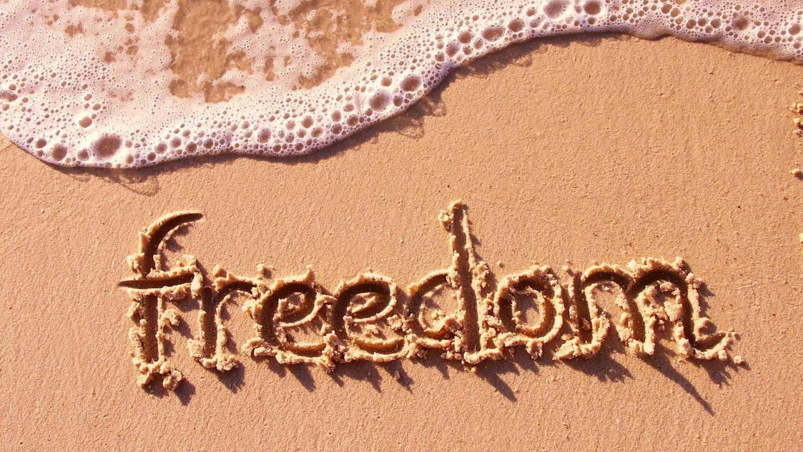 Zee en strand wallpaper met de tekst freedom in het zand geschreven 1600x900