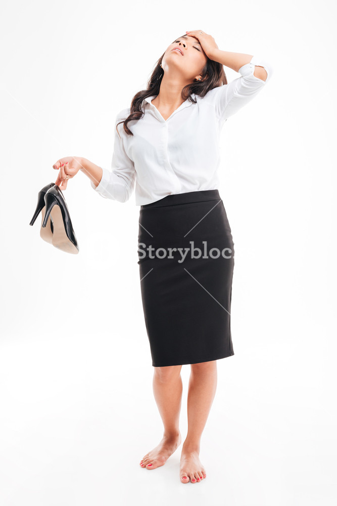 Tired exhausted young asian businesswoman standing barefoot and 667x1000