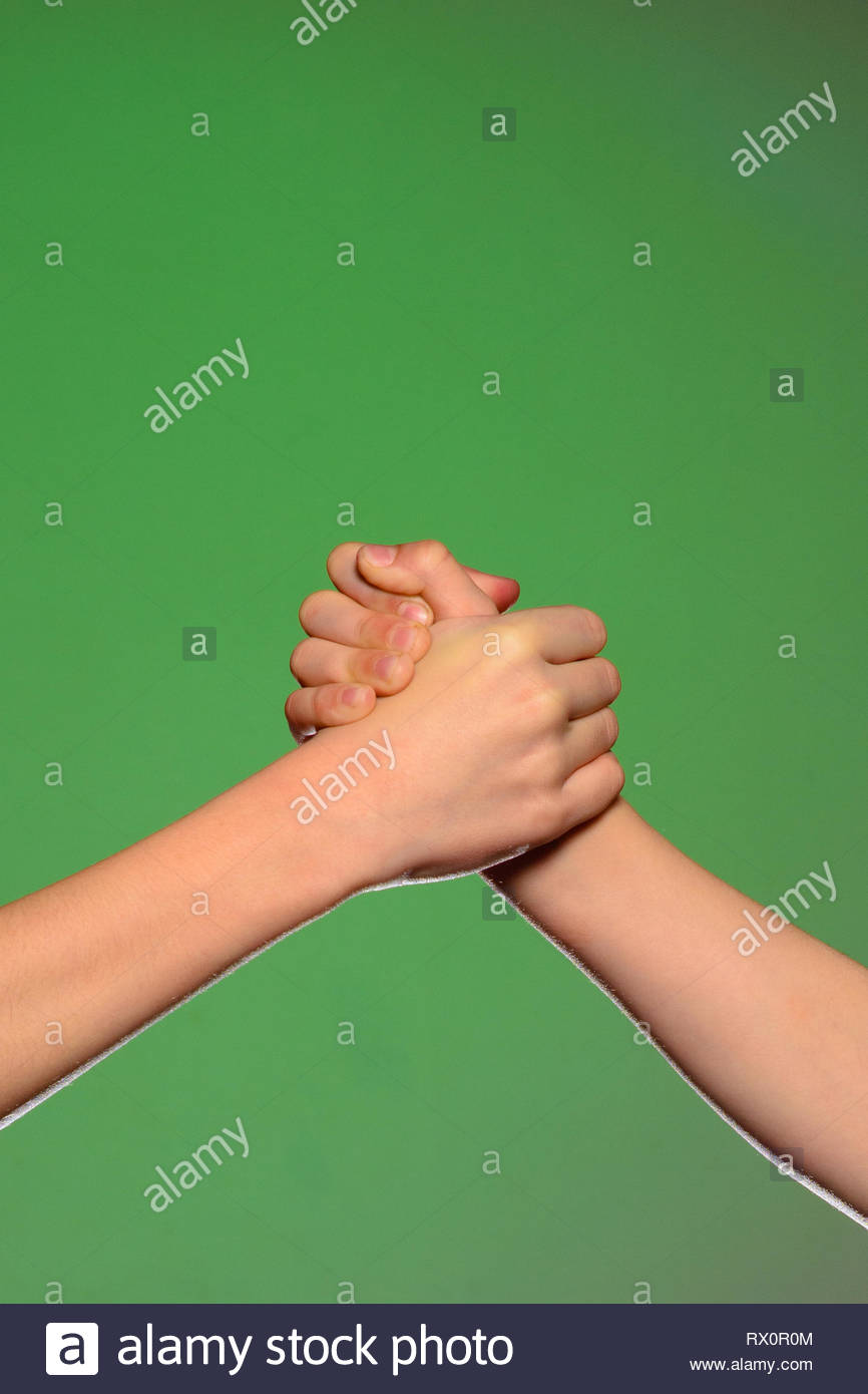 Two hands handshake isolated on a green background symbolizing 866x1390