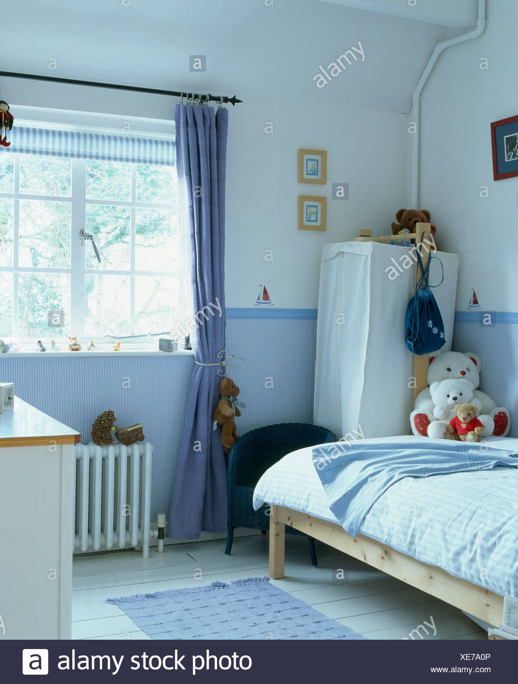 Blue curtain at window in childs bedroom with blue wallpaper dado 1053x1390