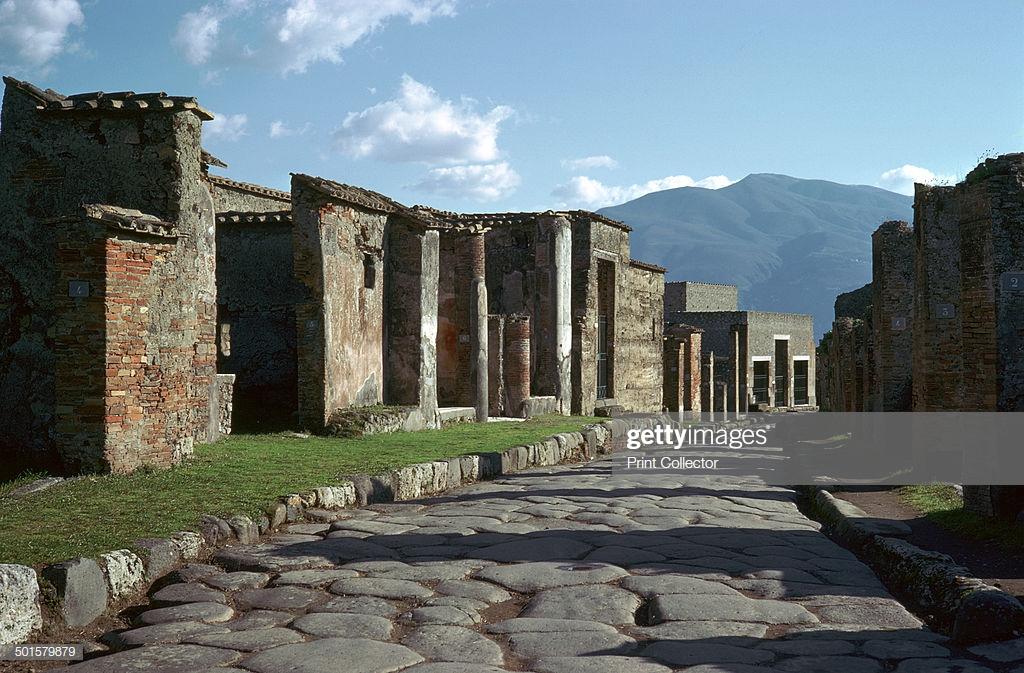 Street scene in Pompeii with Vesuvius in the background 1st 1024x673