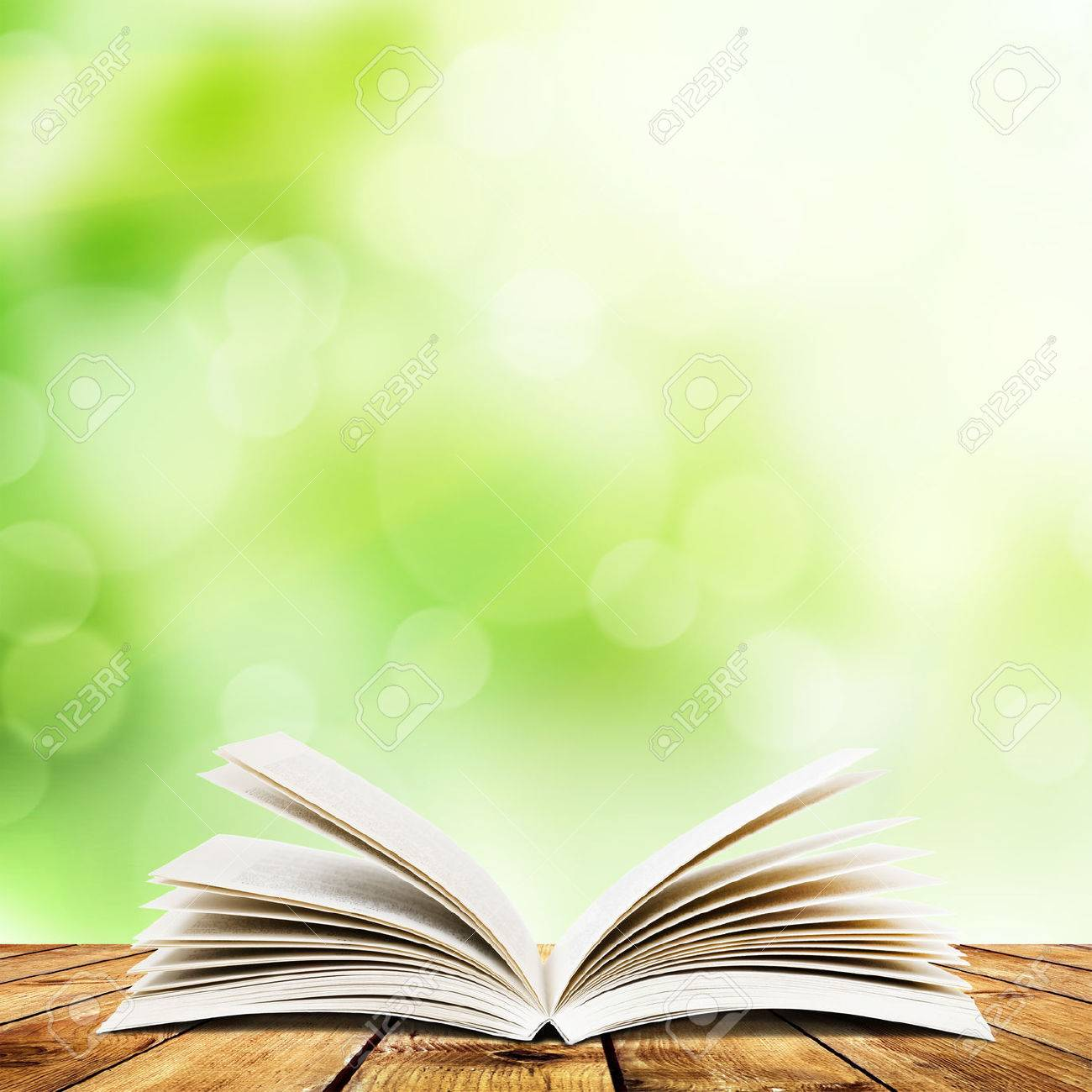 Open Book On Wood Planks Over Abstract Light Background Stock 1300x1300