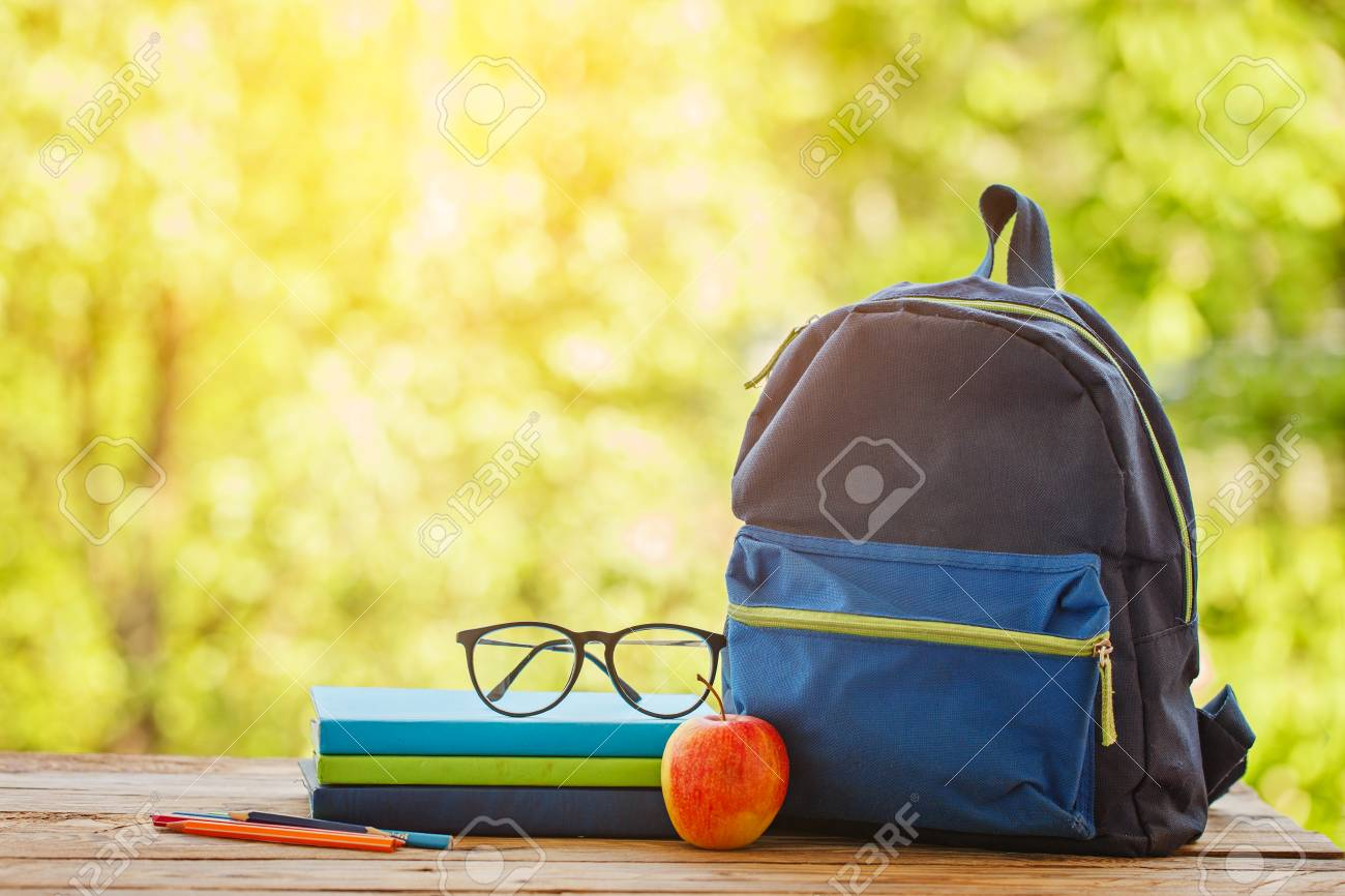 School Backpack With Books On Wooden Table And Nature Background 1300x866