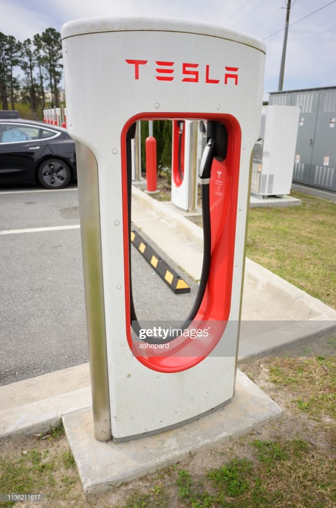 Tesla Supercharger Station With Vehicle Charging In Background 678x1024
