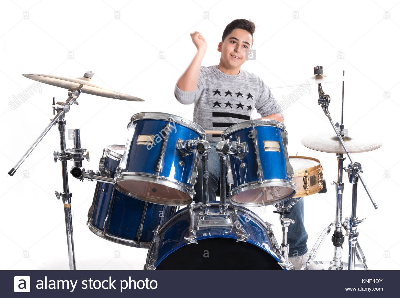 teen boy at drumset in studio against white background Stock Photo 1300x969