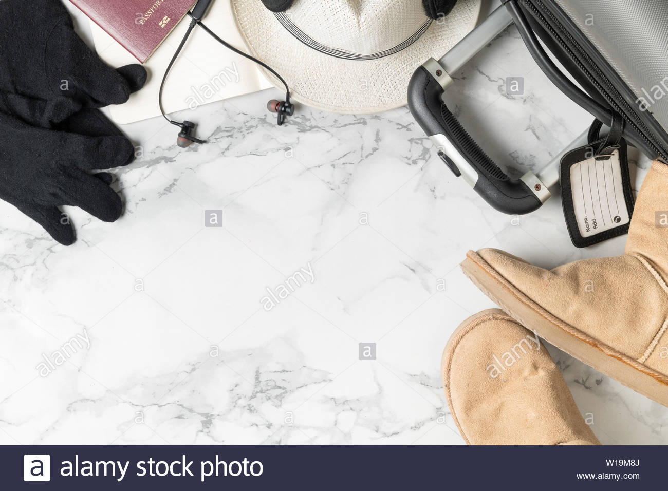 prepare suitcase accessories and travel items for winter on marble 1300x956