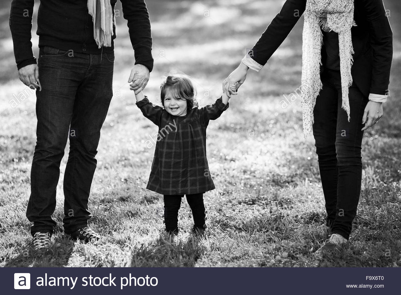 Father Holding Baby Girls Hands Black and White Stock Photos 1300x956