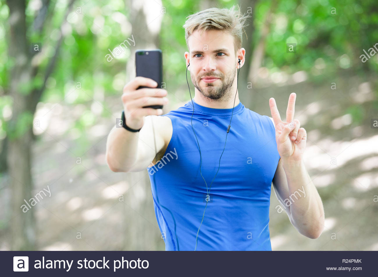 Man athlete concentrated face take smartphone photo nature 1300x955