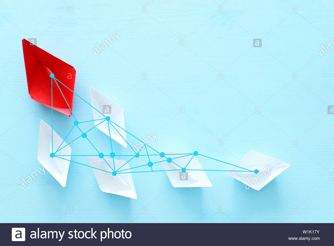 business Leadership concept image with paper boats on blue wooden 1300x956