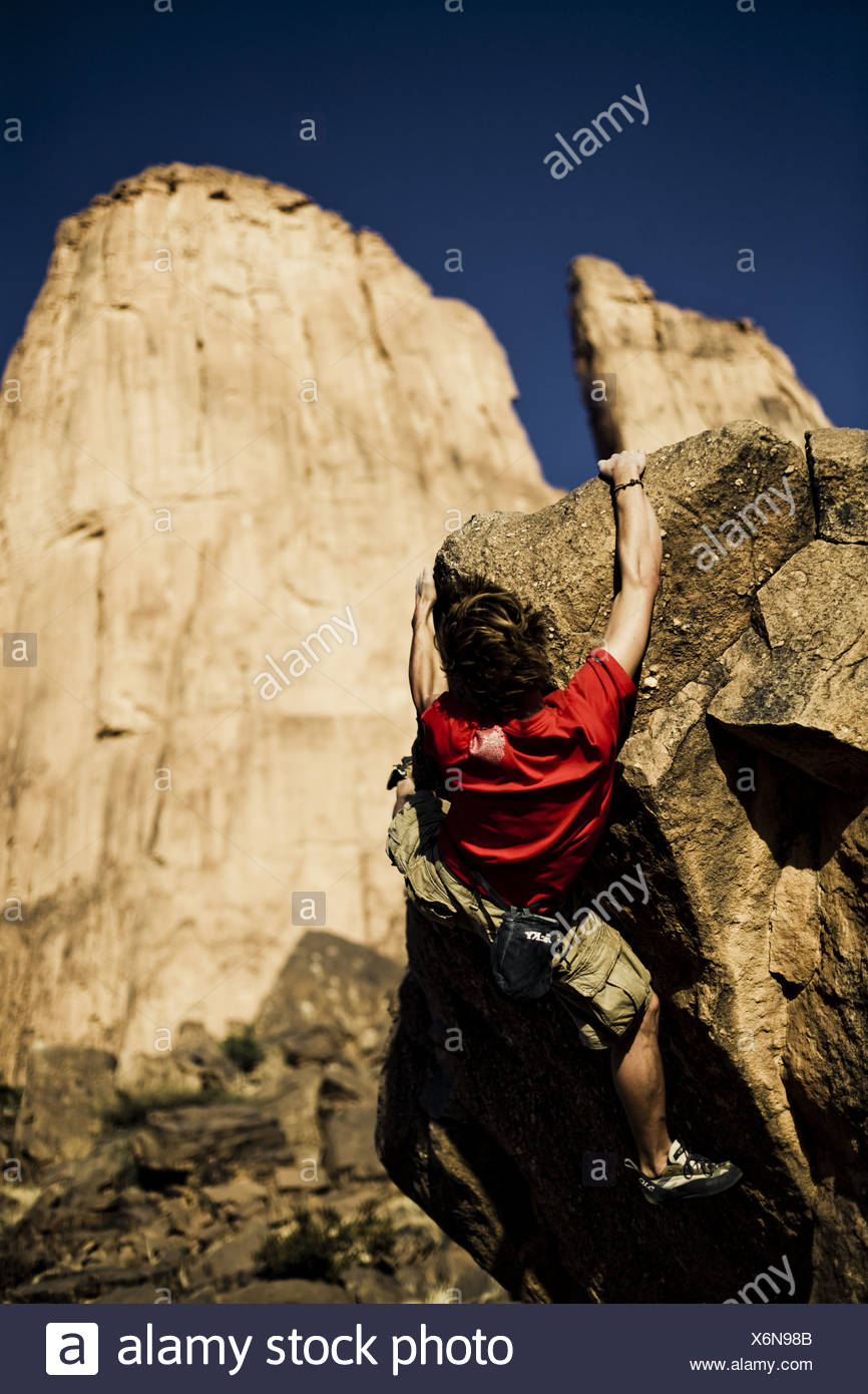 Young man bouldering Hand of Fatima under blue sky in the 866x1390